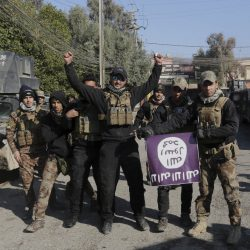 Iraqi special forces troops celebrate as they hold a flag of the Islamic State they captured after regaining control of the Andalus neighborhood on the eastern side of Mosul.