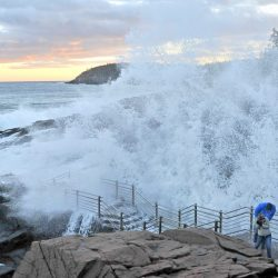 Visitors brace themselves as a wave crashes in Thunder Hole at Acadia National Park in Bar Harbor in January 2014.