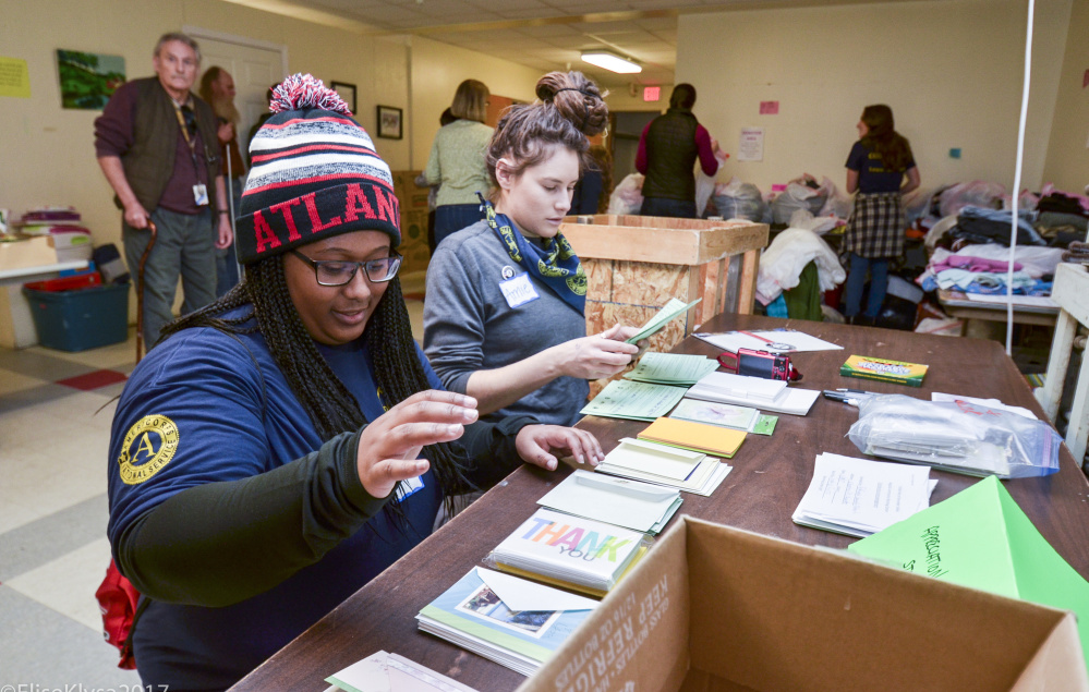 """AmeriCorps VISTA volunteers Rebekah Smith, left, of Decatur, Georgia, and Amie Daniels of Mount Vernon, Maine, volunteer Monday at the Augusta Warming Center. """"The legacy of Dr. King is important,"""" Smith said. """"He's a great man."""""""