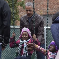 """President Obama pushes kids on the swings as they visit """"Malia and Sasha's Castle"""" that the Obamas donated to the Jobs Have Priority Naylor Road Family Shelter."""