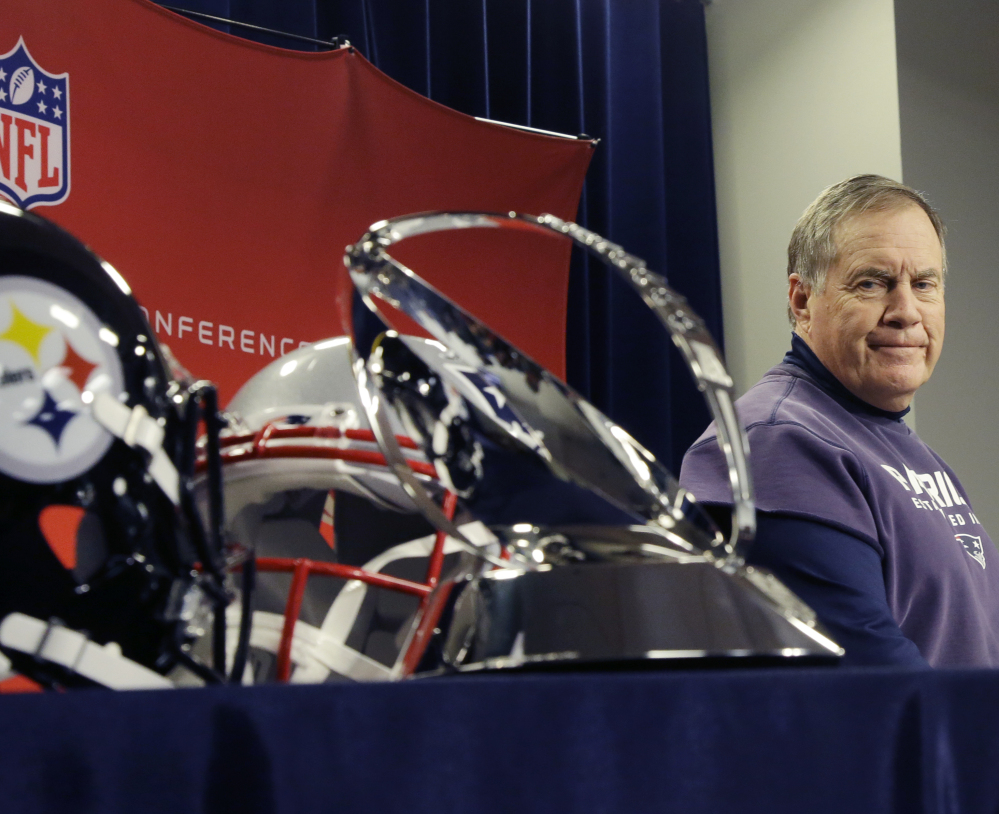Patriots Coach Bill Belichick glances at the Lamar Hunt Trophy that he hopes to hold aloft Sunday night. It goes to the winner of the AFC title game.