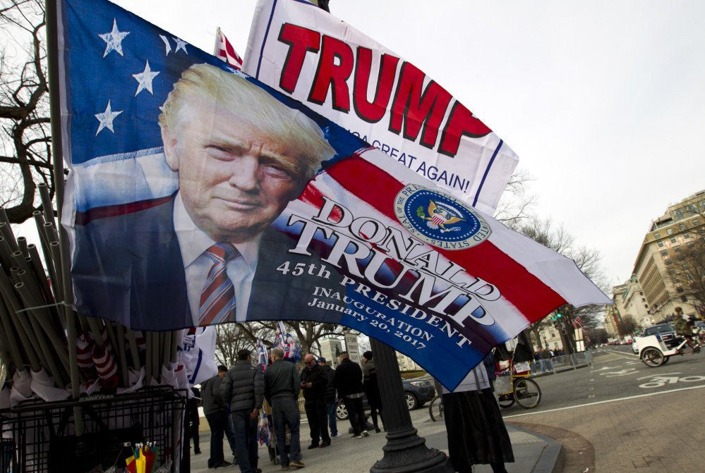 Flags adorned with Donald Trump's visage are for sale Thursday along the Inaugural Parade route on Pennsylvania Avenue in Washington. Inauguration events kicked off Thursday with a concert headlined by Toby Keith at the Lincoln Memorial.