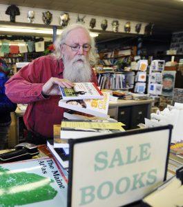 Longtime Maine bookseller and poet Gary Lawless works behind the counter at Gulf of Maine Books in Brunswick.