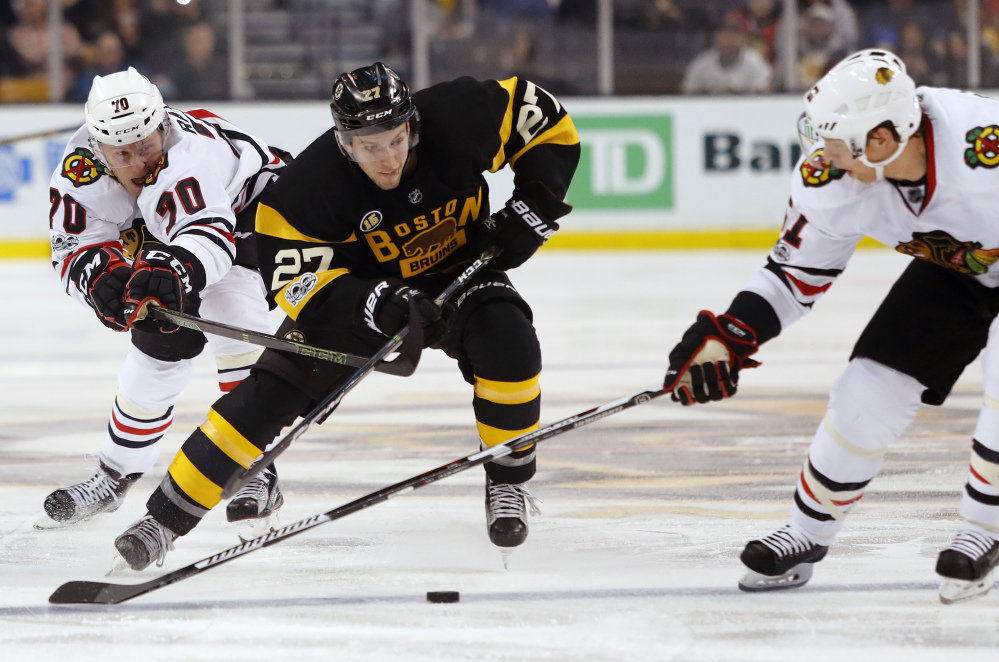 Boston's Austin Czarnik tries to cut between Chicago's Dennis Rasmussen, 70, and Brian Campbell in the second period Friday night in Boston.