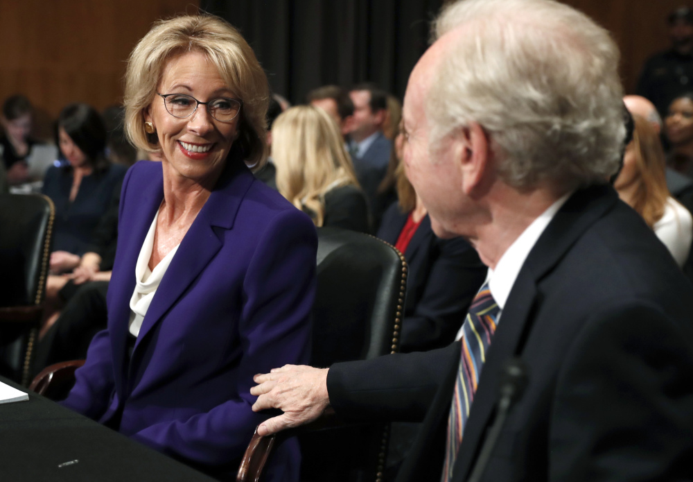 Education Secretary-designate Betsy DeVos talks to Joe Lieberman at her confirmation hearing on Tuesday. Freshman Sen. Maggie Hassan of N.H. tossed her some tough questions.