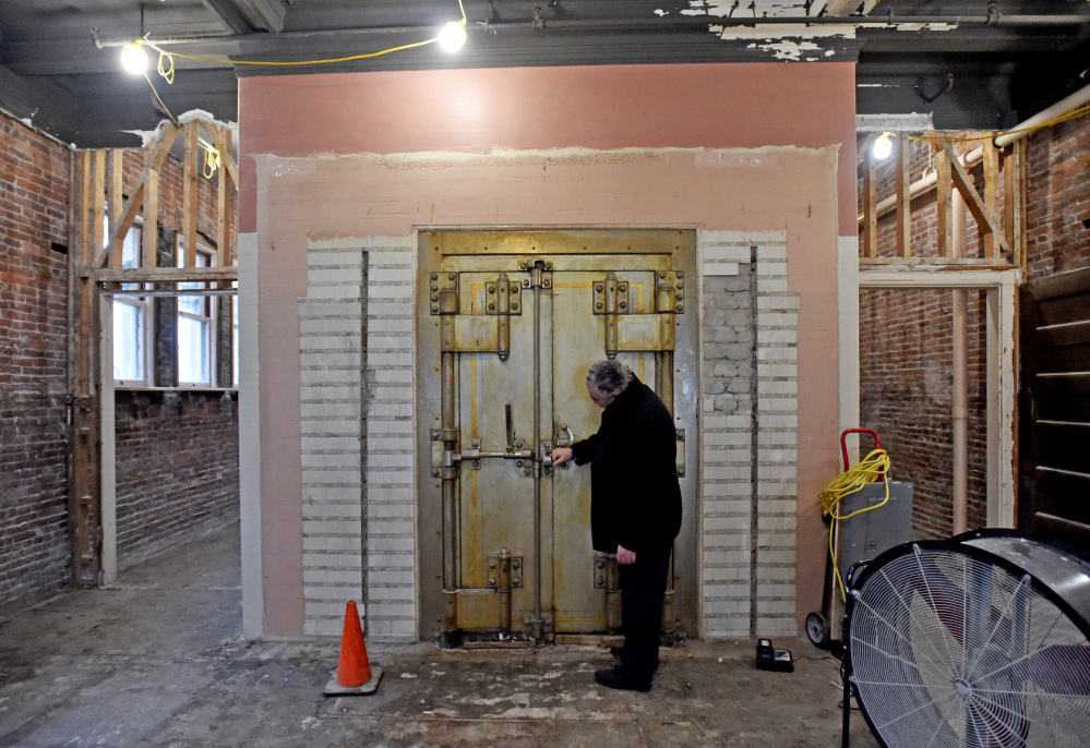 Paul Ureneck, director of commercial real estate for Colby College, inspects the 1902-era safe from the former Waterville Savings Bank that first occupied the former Hains Building, which is being renovated as part of a $5 million project.
