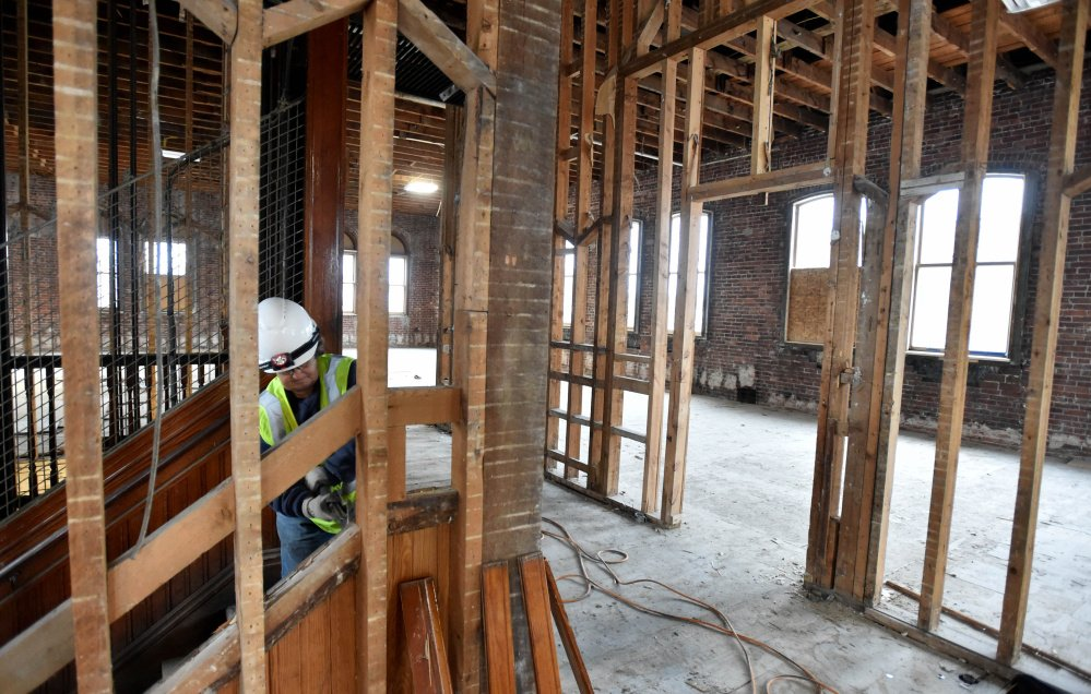 Connie Damboise and Ken Theriault work on the top floor of the former Hains Building on Main Street in Waterville on Friday. The building at 173 Main St. is being renovated as part of a $5 million project.