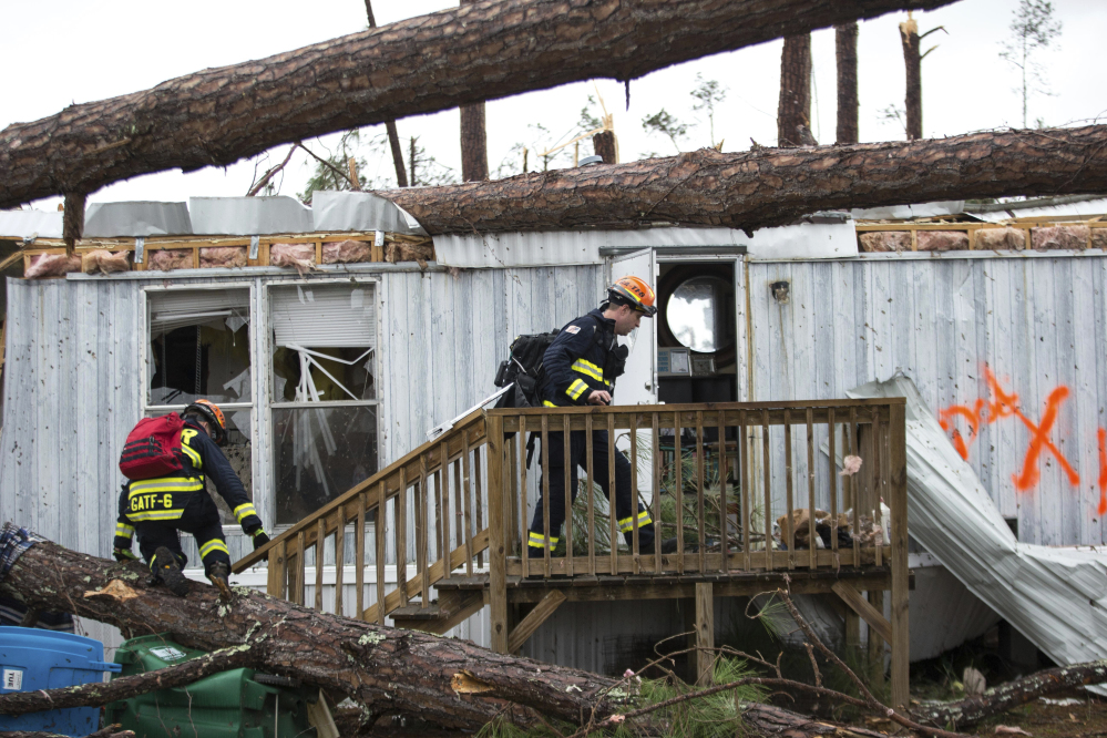 Rescue workers prepare to enter a mobile home Monday to search for survivors at Big Pine Estates after it was damaged by a tornado in Albany, Ga. Fire and rescue crews were searching through the debris Monday, looking for people who might have become trapped when the storm came through.