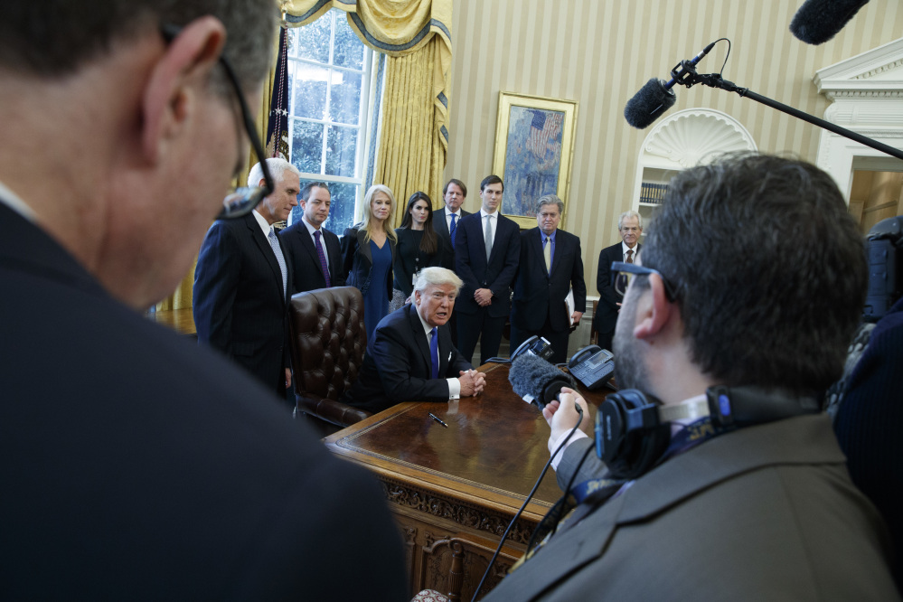 President Trump answers a question after signing a series of executive orders on Tuesday in the Oval Office of the White House in Washington. The administration has instructed officials at the Environmental Protection Agency to freeze its grants and contracts, and to black out all media communications.