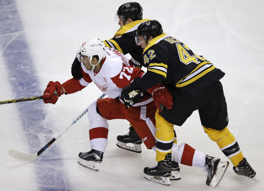 Red Wings center Andreas Athanasiou is held back by Boston's David Backes, right, and Frank Vatrano in the first period Tuesday night in Boston.