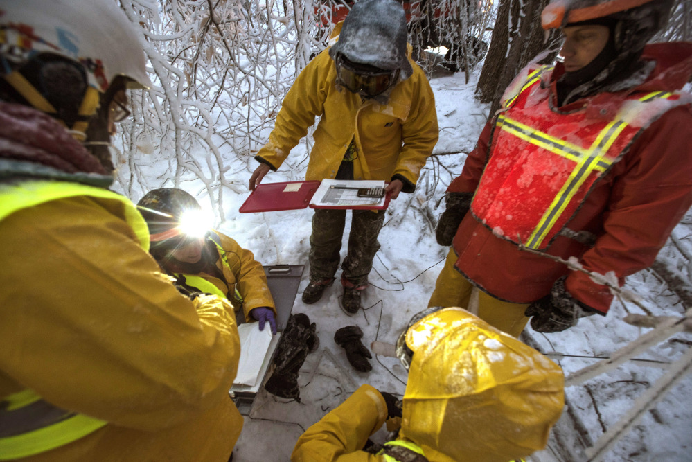 Researchers gather to measure ice accumulation on wooden collectors in the Hubbard Brook Experimental Forest in Woodstock, New Hampshire this month. Scientists have been creating ice storms there to help understand the effects of ice on northern forests.