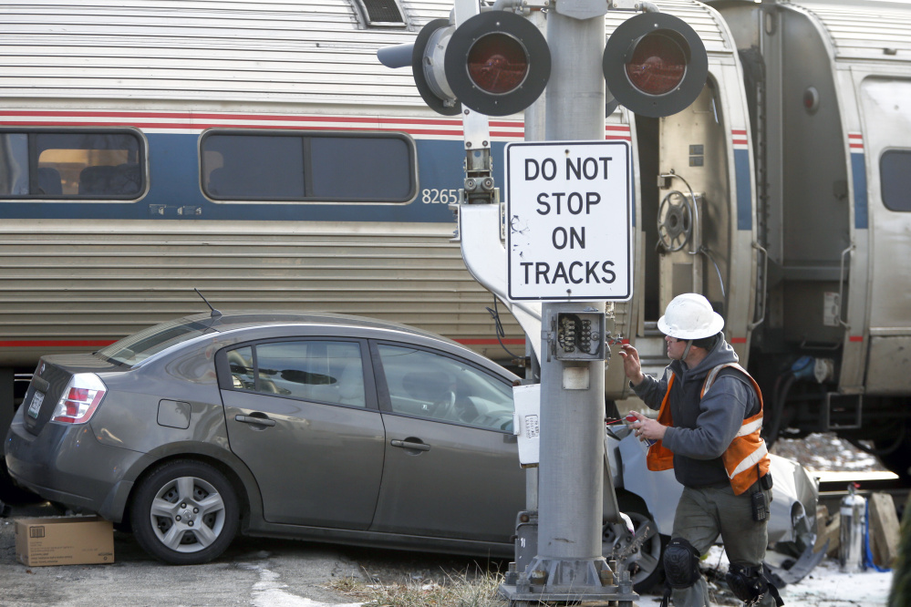 A repairman works on the railroad crossing signal on Brighton Avenue after Friday's crash. Police say the Nissan Sentra collided with the Downeaster when the driver tried to outrace the train.