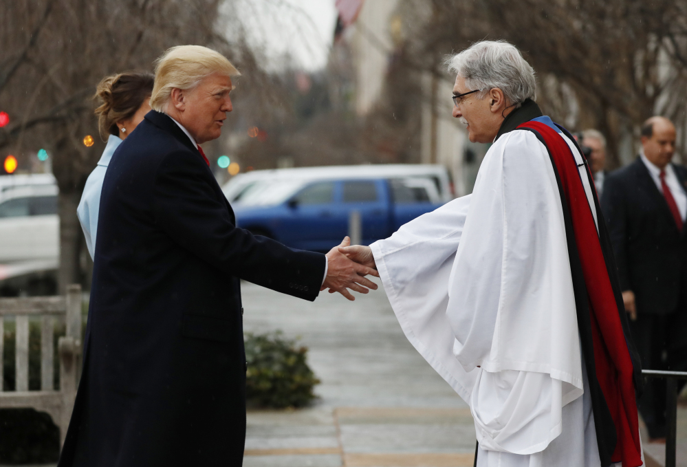 Rev Luis Leon greets President-elect Donald Trump and his wife Melania as they arrive for a church service at St. John's Episcopal Church across from the White House in Washington, Friday, Jan. 20, 2017, on Donald Trump's inauguration day. (AP Photo/Alex Brandon)