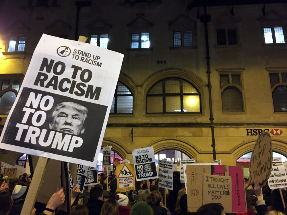 Demonstrators hold banners during a protest against U.S President Donald Trump's controversial travel ban on refugees and people from seven mainly-Muslim countries, in Oxford, England, Monday.
