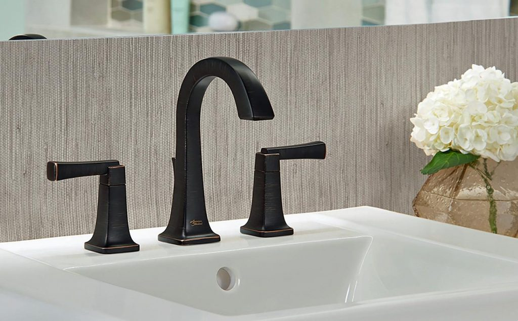 The distinctive high-arc American Standard Townsend widespread bathroom sink faucet with accessible lever handles is featured here in a dramatic Legacy Bronze finish.