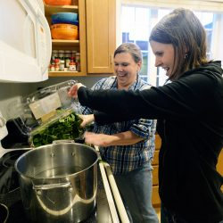 Anna Bulger, right, adds spinach to a pan while cooking with house manager Nicole Merrill. The housing project that opened in the Knightville neighborhood in 2010.