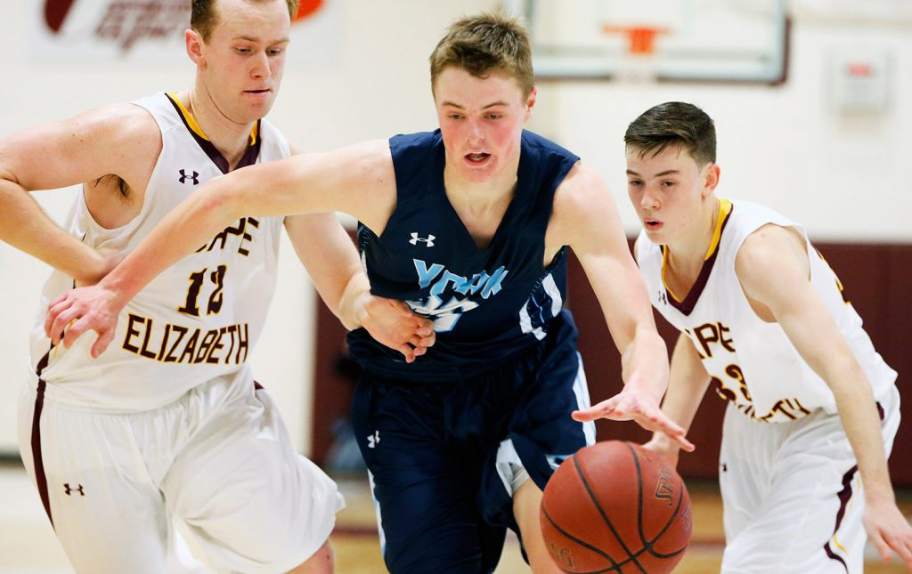 York senior Trevor LaBonte runs the ball through Cape Elizabeth's Quinn Hewitt (12) and Jacob Allen during Monday night's game at Cape Elizabeth. Labonte had 23 points and 15 rebounds in the game.