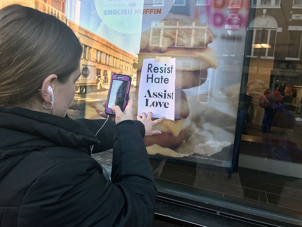 Sarah Muehle of Portland takes a photo of one of the signs that appeared in storefronts along Congress Street Friday morning.