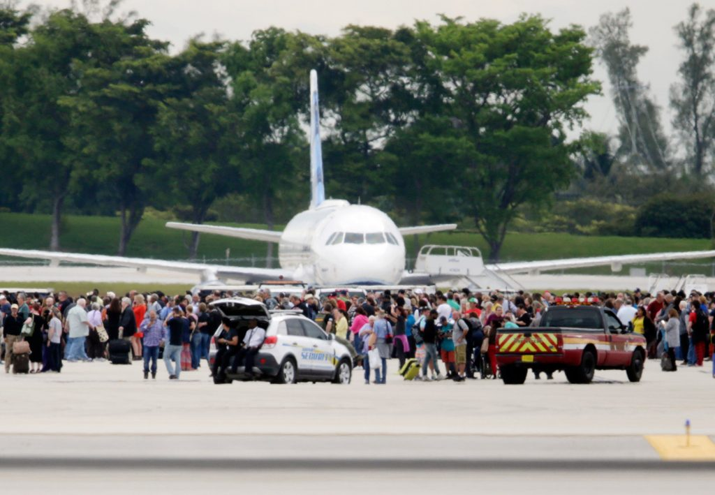 People stand on the tarmac at Fort Lauderdale-Hollywood International Airport on Friday after a man opened fire inside a terminal, killing five people and wounding eight before being taken into custody.