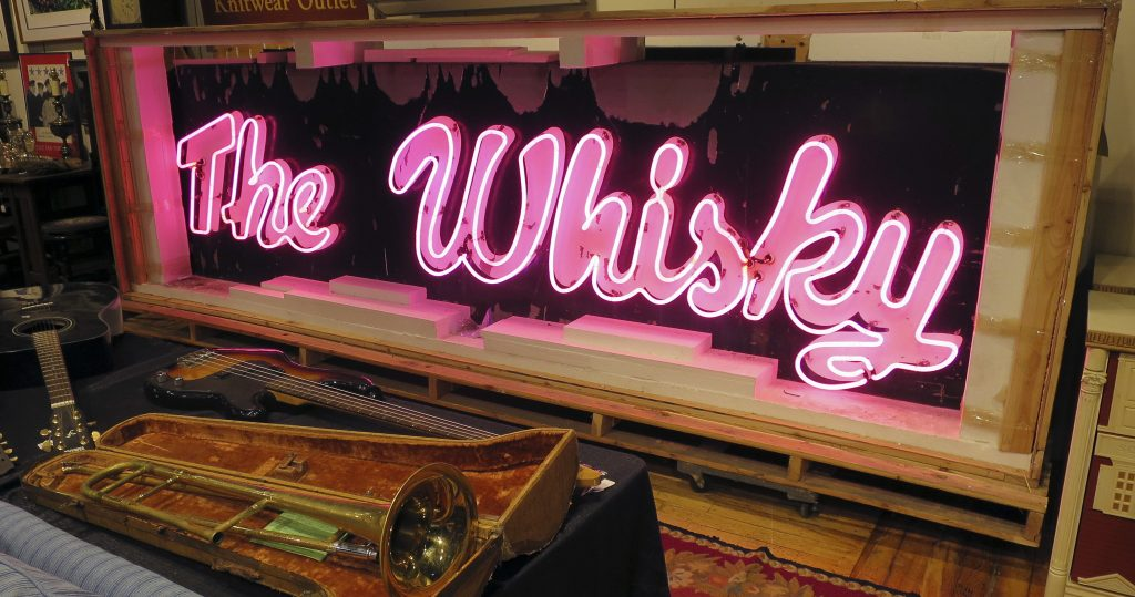 A marquee from the legendary Whisky a Go Go glows at the Saco River Auction Co. in Biddeford, where it sold Wednesday night for $43,000.