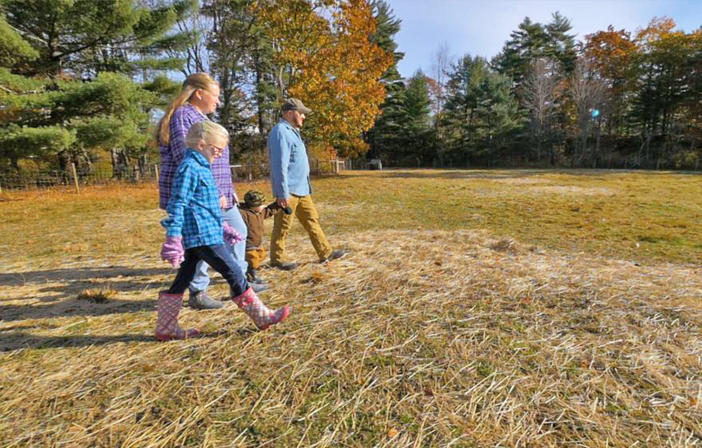"Walter and Aaron Morse, with their children Paige and Joseph, walk through a field at their Patriot Ridge Homestead in Jefferson. The family will be featured Sunday on the first episode of a new a television show called ""Growing Home,"" about veterans working in agriculture throughout Maine. <em>Photo courtesy of Up Country Productions</em>"