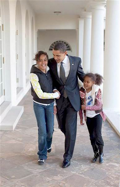 President Obama walks down the White House Colannade with his two daughters in this undated White House photo.