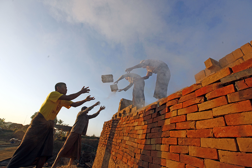 """Workers unload bricks at a brick-making factory in Naypyitaw, Myanmar.  """"It is obscene for so much wealth to be held in the hands of so few when 1 in 10 people survive on less than $2 a day,"""" says Winnie Byanyima, executive director of Oxfam International. """"Inequality is trapping hundreds of millions in poverty; it is fracturing our societies and undermining democracy."""""""