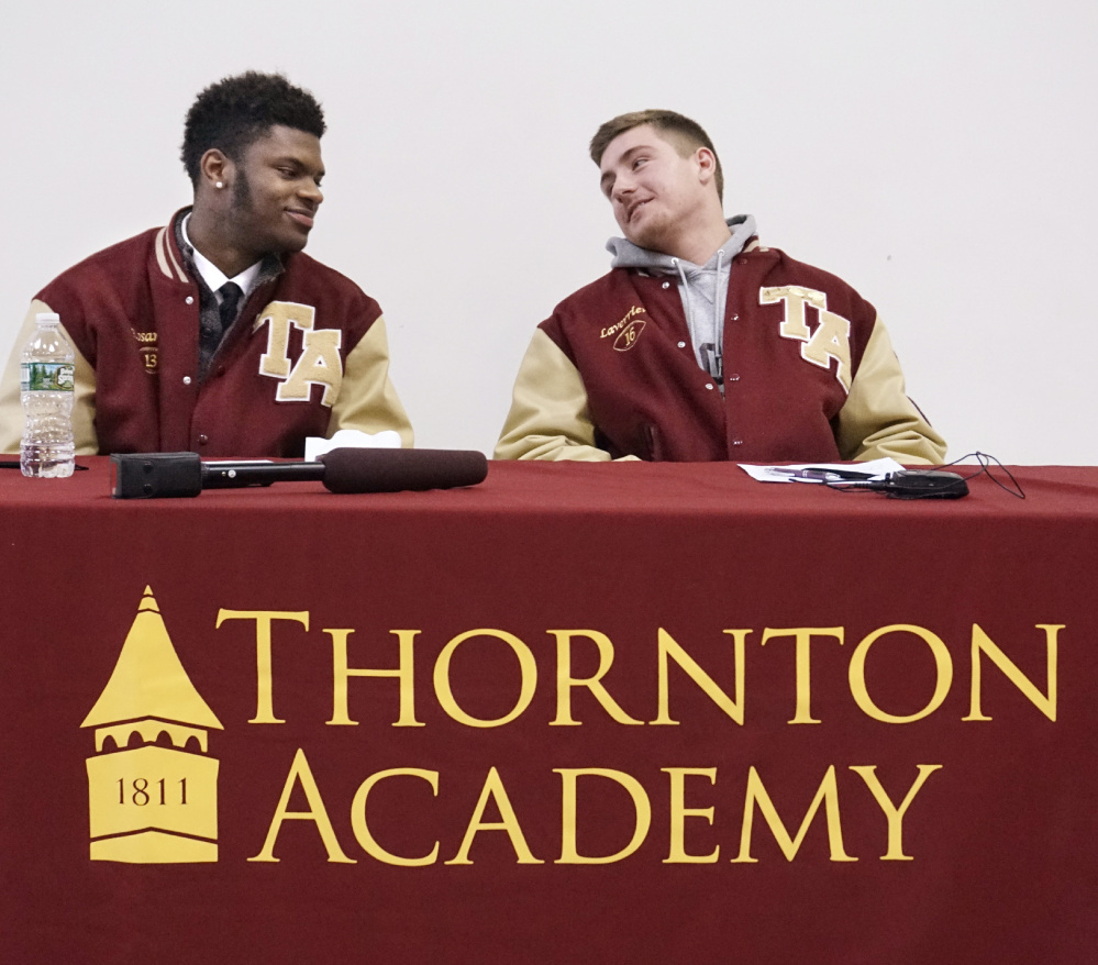 Johnny Rosario, left, and Michael Laverriere share the podium at Thornton Academy after signing letters of intent to play football at UMaine.