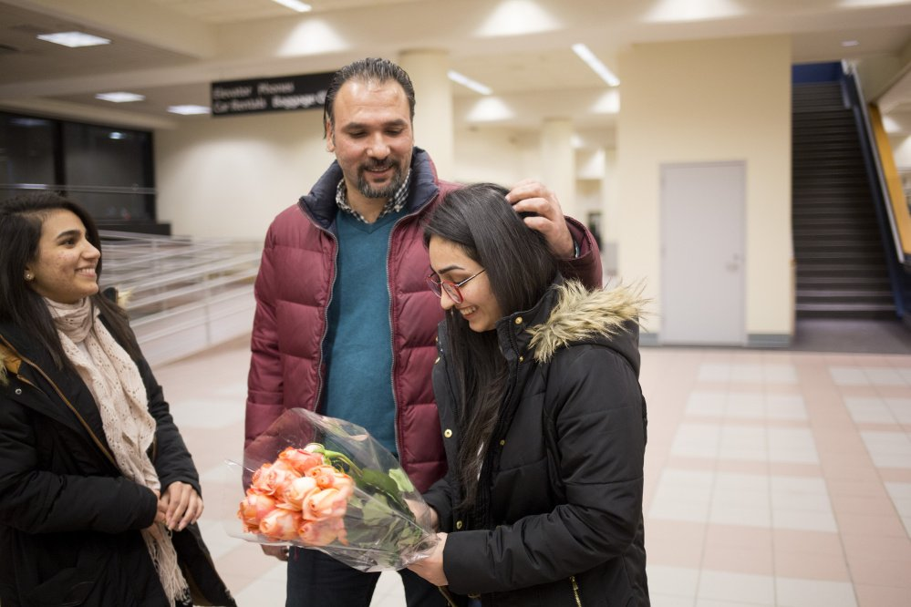 Banah Al-Hanfy, right, her uncle Aqeel Mohialdeen and her sister Jumana Al-Hanfy wait for U.S. Rep. Chellie Pingree to join them at the Portland airport on Feb. 3. Pingree's office and others from various organizations worked together to help get Al-Hanfy reunited with her family.