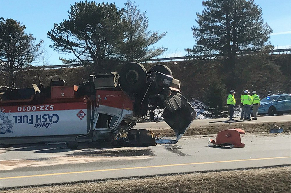 An oil tanker rests on its top in the northbound lanes of I-295 in South Portland late Monday morning.