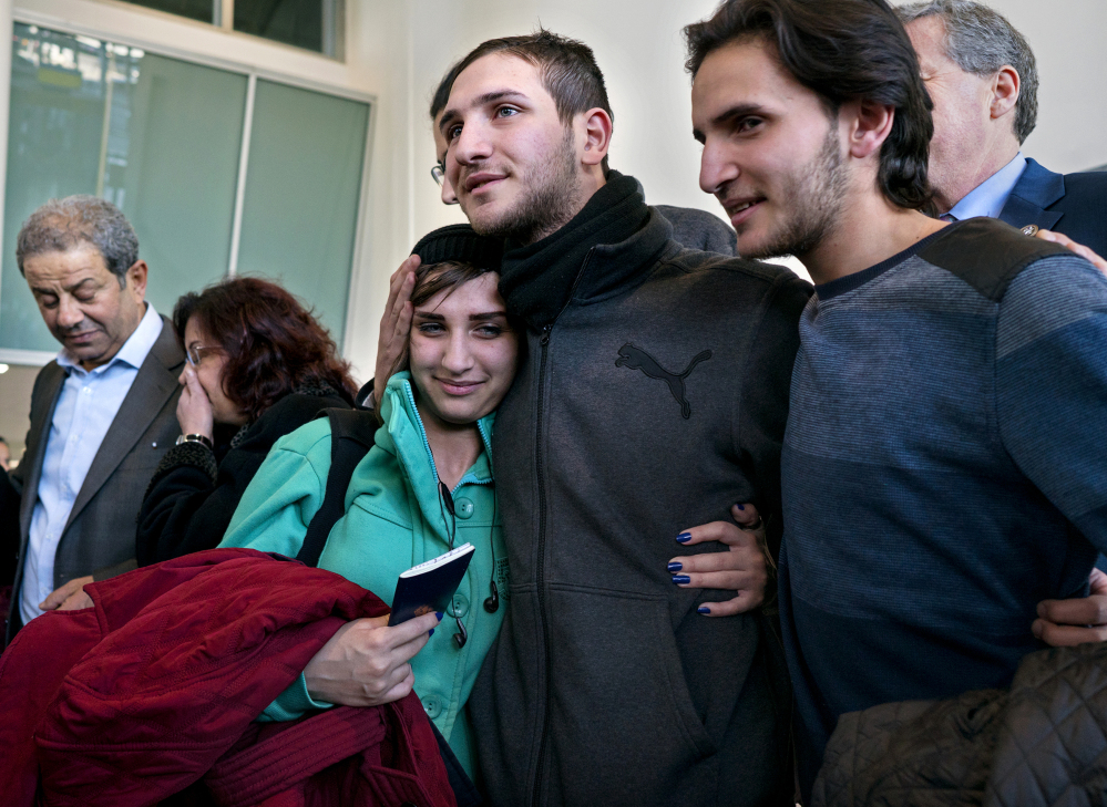 Tawfik Assali, 21, center, of Allentown, Pa., embraces his sister Sarah Assali, 19, upon her and other family members' arrival from Syria at at John F. Kennedy International Airport in New York on Monday. At right is Mathew Assali, 17, who arrived Monday. Attorneys said members of the Assali family returned to Syria after they were denied entrance to the United States on Jan. 28 although they had visas in hand after a 13-year effort.