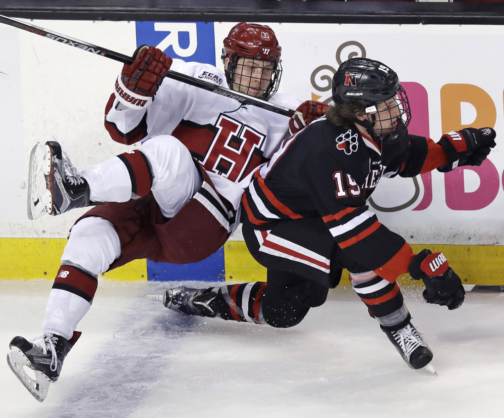 Harvard's Michael Floodstrand, left, is tripped up by Northeastern's Lincoln Griffin during the second period of Harvard's 4-3 win in a semifinal game of the Beanpot tournament Monday at Boston.
