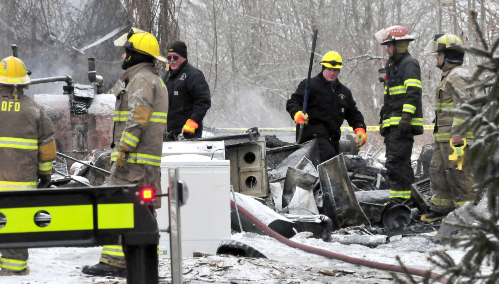 State officials and local firefighters examine the section of an apartment building on Square Road in Palmyra where the bodies of two tenants were recovered Tuesday.