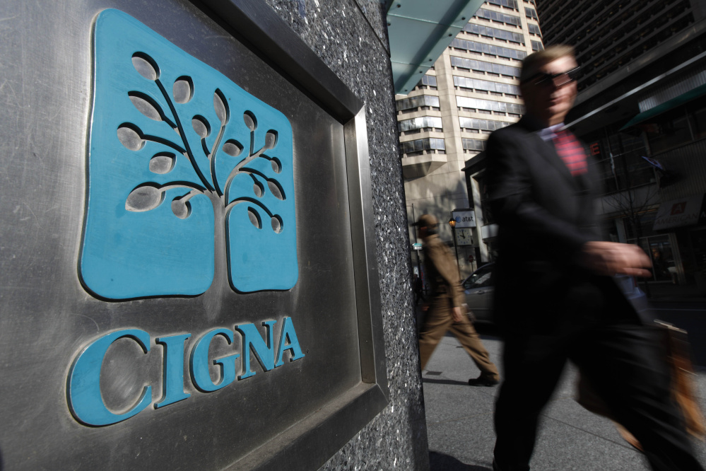 A pedestrian walks past the headquarters of health insurer Cigna Corp. in Philadelphia. A federal judge Wednesday rejected Anthem Inc.'s bid to buy rival health insurer Cigna Corp., saying the merger would likely lead to higher costs, less competition and diminished innovation. U.S. District Judge Amy Berman Jackson said the merger would significantly reduce competition in the already concentrated insurance market, particularly for large national employers.
