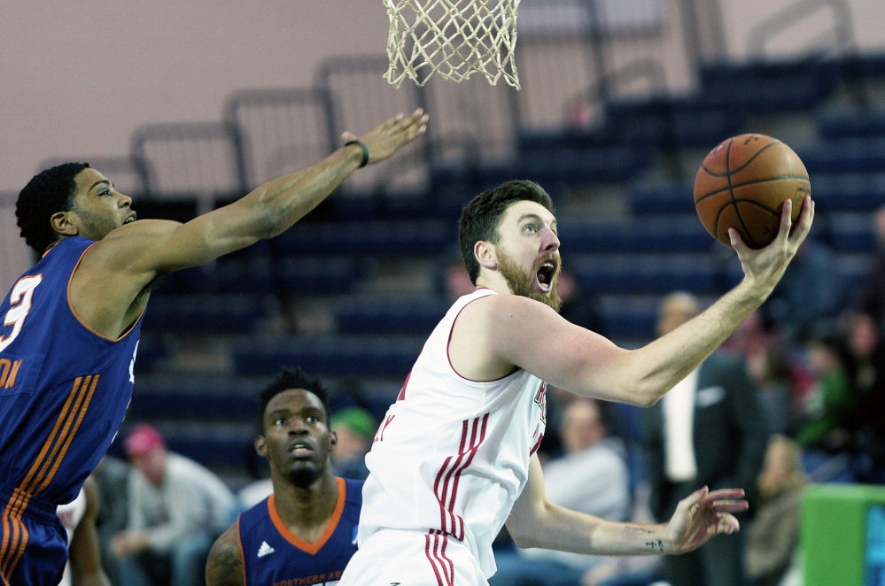 Ryan Kelly of the Maine Red Claws drives to the basket as Shaquille Harrison of the Northern Arizona Suns attempts to block Kelly's shot during Thursday's game at the Portland Expo. Maine won, 97-91. (Photo by Shawn Patrick Ouellette/Staff Photographer)