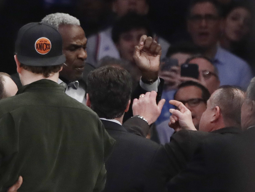 Charles Oakley, a former player for the New York Knicks, exchanges words with a security guard Wednesday night at a Knicks game. Oakley was arrested for three counts of misdemeanor assault and one count of criminal trespass.
