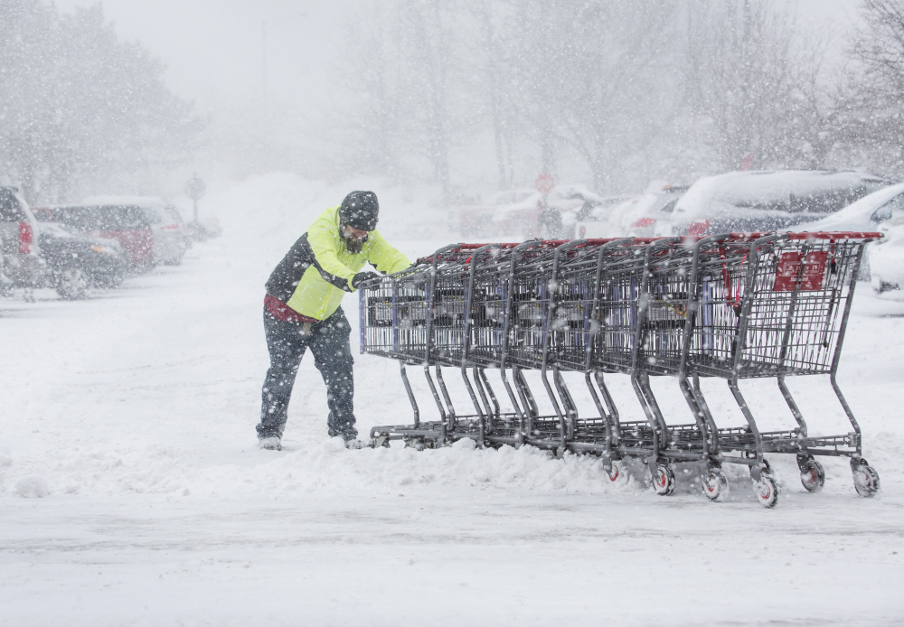 Mike Scarpelli collects shopping carts at Hannaford in Portland during Thursday's snowstorm. Hardware stores reported brisk sales of shovels and snowblowers ahead of the storm, which dumped 7.5 inches of snow in Portland and more in York County. At Portland International Jetport, 70 percent of flights were canceled Thursday, and more travel disruptions are expected as another storm moves in Sunday night.