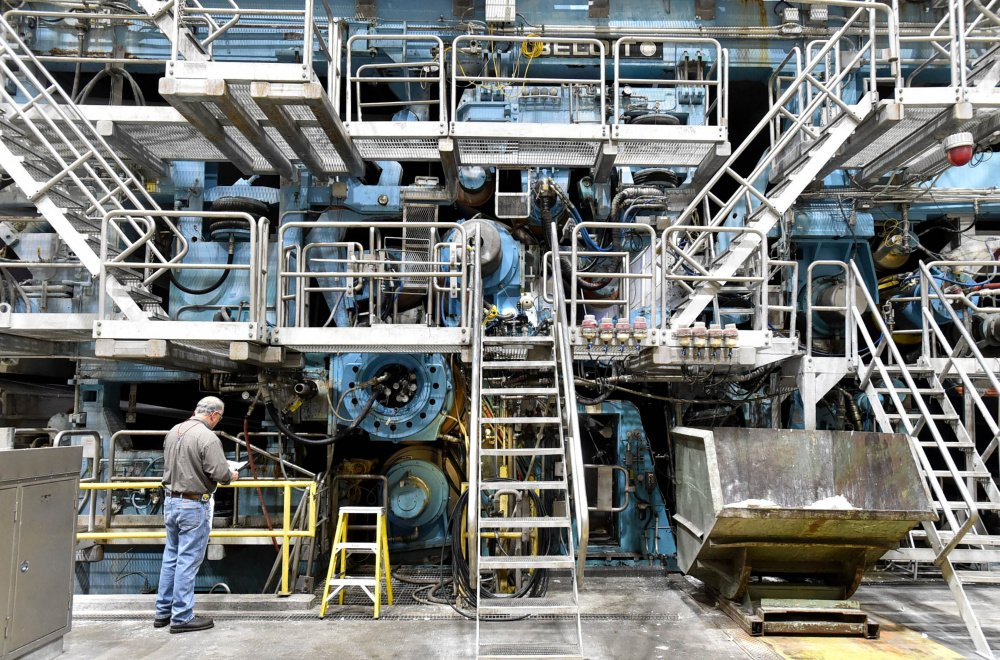 A worker inspects machine No. 2 on Friday at the Sappi paper mill in Skowhegan. Sappi has announced a $165 million upgrade of another paper machine at the Somerset County facility.