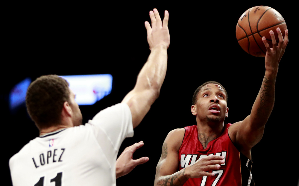 Miami guard Rodney McGruder goes up for a shot against Brooklyn center Brook Lopez during the first half of their game Friday night in New York. The Heat captured their 13th straight win, 108-99.