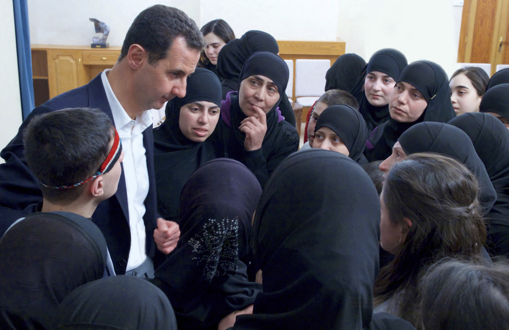 Syrian President Bashar Assad meets with former hostages released in a prisoner exchange with rebels in Damascus, Syria. Assad appears to be immune to consequences as evidence of atrocities continues to mount.