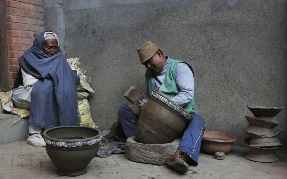 Potter Bishnu Bahadur Prajapati, 53, works on a clay pot, as a neighbor looks on in the Nepali town of Thimi. Potters used to travel to sell their wares, but that tradition is dead.