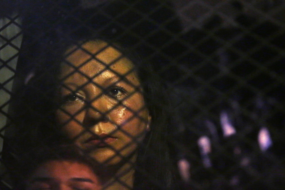 Rob Schumacher/The Arizona Republic via AP Guadalupe Garcia de Rayos is locked in a van that is stopped in the street by protesters outside the Immigration and Customs Enforcement facility Wednesday in Phoenix. Apparently fearing her deportation, activists blocked the gates surrounding the office in what the Arizona Republic says was an effort to block several vans and a bus inside from leaving.
