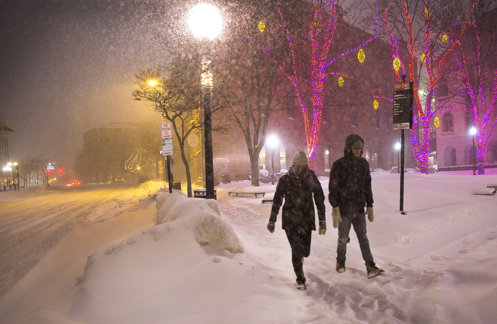 Cara Benge, left, and Nate Mosseau walk during the early hours of the blizzard Sunday evening in an almost deserted downtown Portland. They were going to meet friends after seeing Oscar film shorts.
