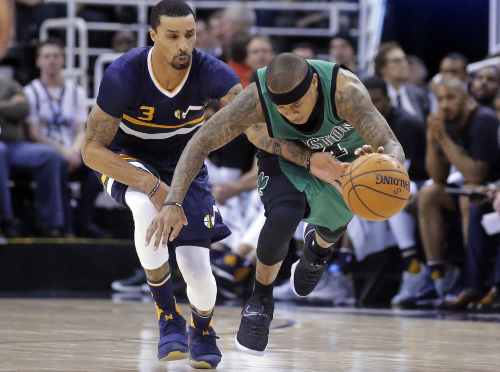 Utah Jazz guard George Hill defends as Boston guard Isaiah Thomas, right, drives up the court during the second half Saturday in Salt Lake City. The Celtics won 112-104.