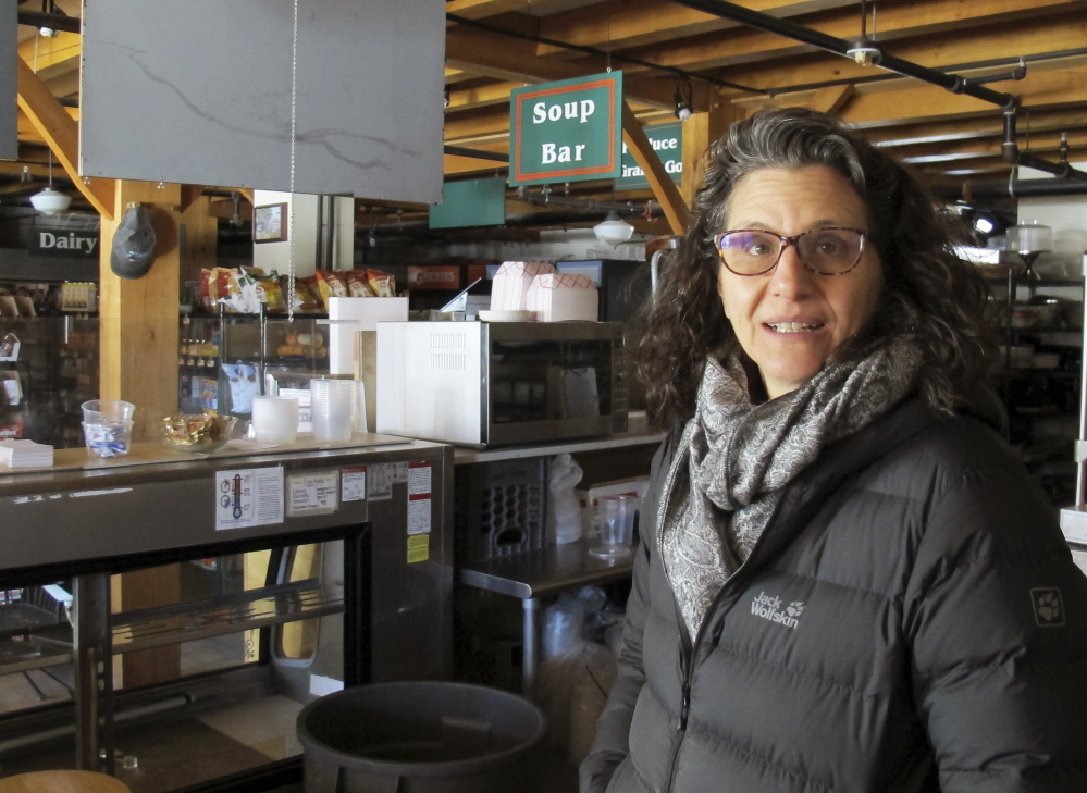 Lyssa Papazian of the Putney Historical Society stands on a balcony of the closed Putney General Store in Putney, Vt. The store was heavily damaged by fire in 2008 and a year later was destroyed by an arson fire. It was rebuilt, but now the store is closed again after the death of its pharmacist.