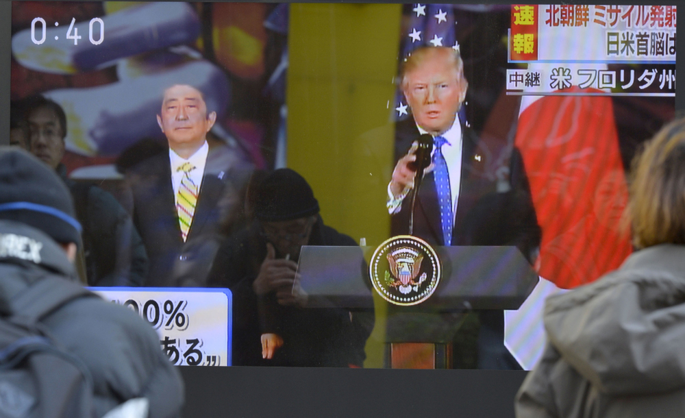People watch a TV screen in Tokyo showing a live broadcast from Florida of a news conference by President Trump and Japanese Prime Minister Shinzo Abe about a missile launch by North Korea on Sunday. Yoshitaka Sugawara/Kyodo News via AP