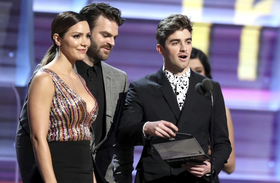From left, Katharine McPhee and The Chainsmokers' Alex Pall and Drew Taggart present the award for best rock song Sunday at the 59th annual Grammy Awards in Los Angeles.