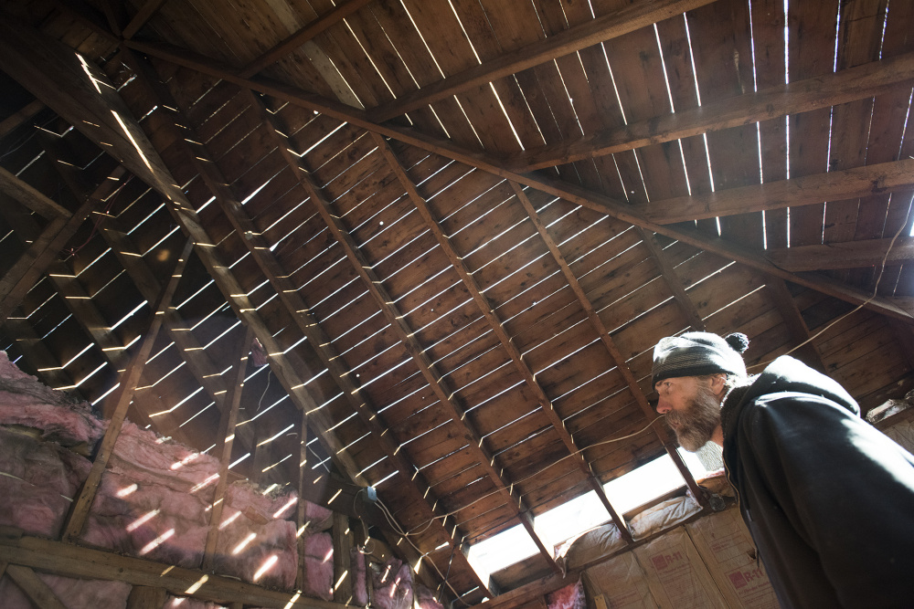 Brett Trefethen of Barn Boards and More last week inspects a second floor room, where wood is being reclaimed by his company at 18 Dennis St. in Gardiner, the former estate of Frank E. Boston.