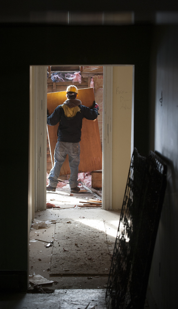A worker employed by Barn Boards and More removes a door last week on the second floor of 18 Dennis St. in Gardiner, the former estate of Frank E. Boston.