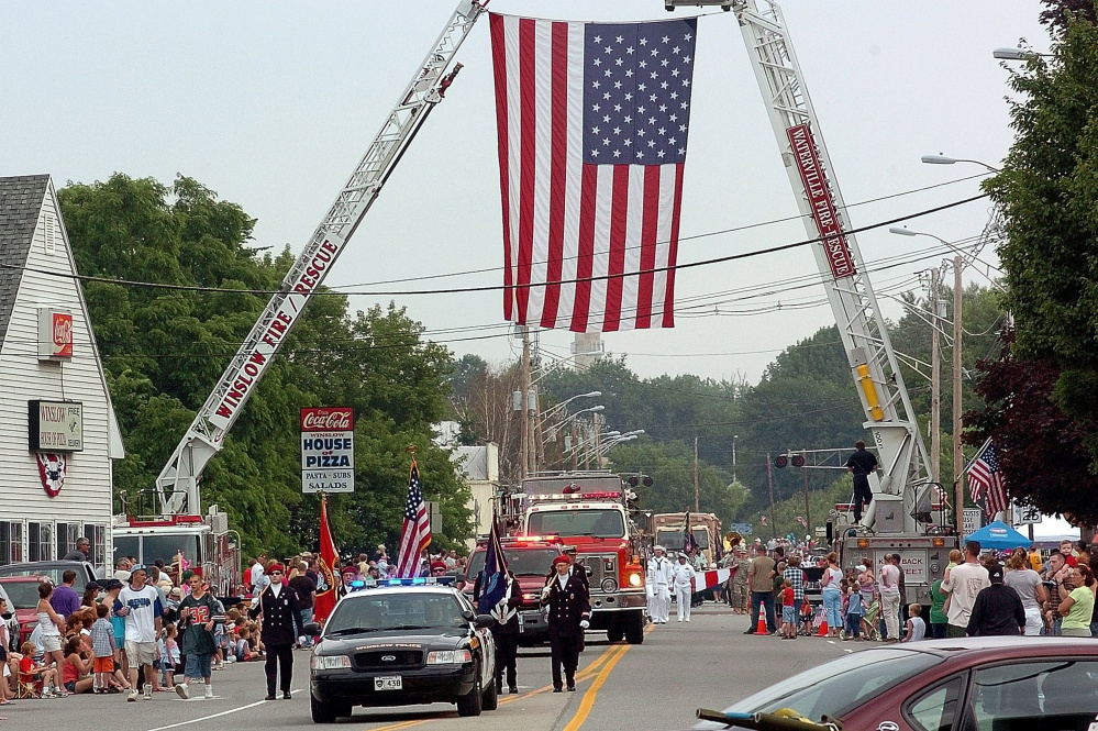 Participants in a previous Winslow Fourth of July parade pass under a huge American flag on Bay Street suspended by ladder trucks from the Winslow and Waterville fire departments. Event organizers aren't sure where the celebration will be held this year, if at all.